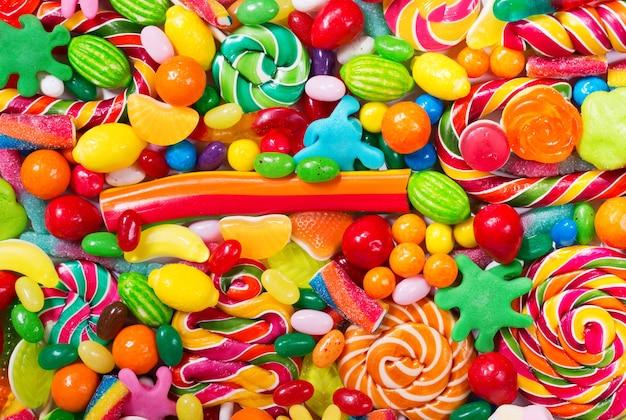 Verschiedene bunte bonbons, gelees, lutscher und marmelade als hintergrund, draufsicht Premium Fotos