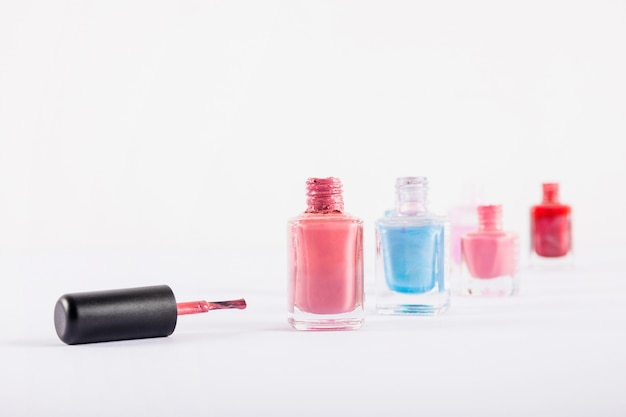 Verschiedene bunte nagellackflaschen getrennt auf weißem hintergrund Kostenlose Fotos