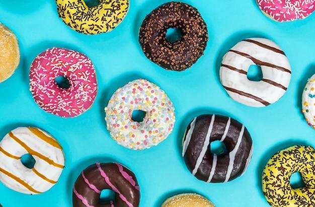 Verschiedene donuts mit verschiedenen füllungen und zuckerguss auf einem blauen rücken Premium Fotos