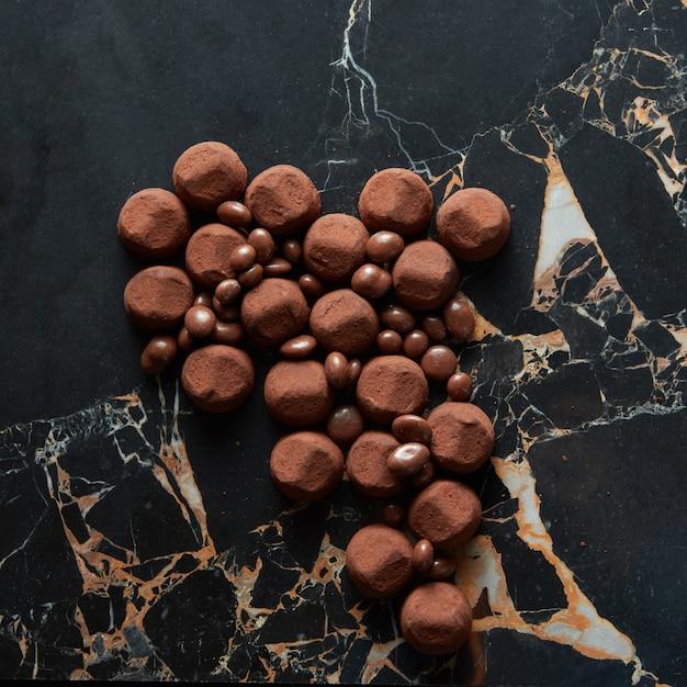 Verschiedene dunkle schokoladentrüffel mit kakaopulver und keks auf dunkler marmoroberfläche Premium Fotos