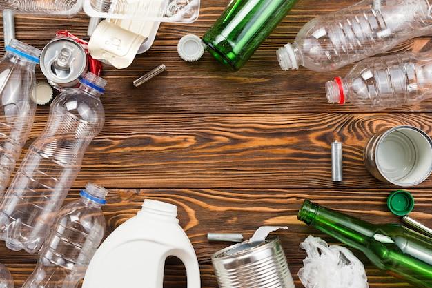 Verschiedene flaschen und müll für die wiederverwertung auf dem tisch Kostenlose Fotos