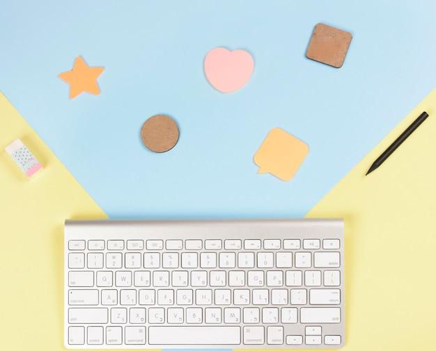 Verschiedene formen mit bleistiften; radiergummi und tastatur auf blauem und gelbem hintergrund Kostenlose Fotos