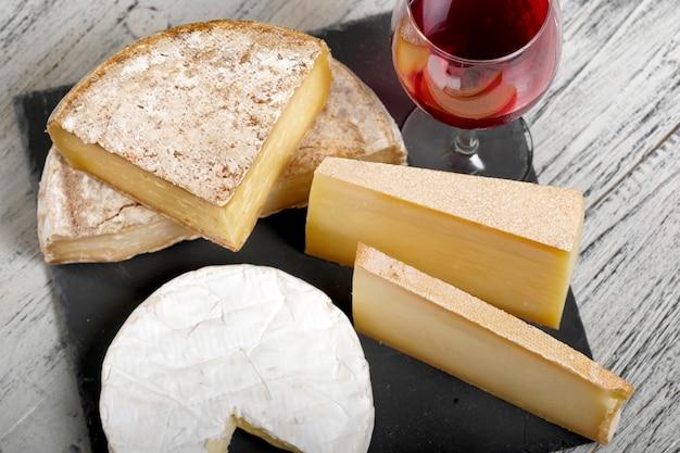 Verschiedene französische käsesorten mit einem glas wein Premium Fotos