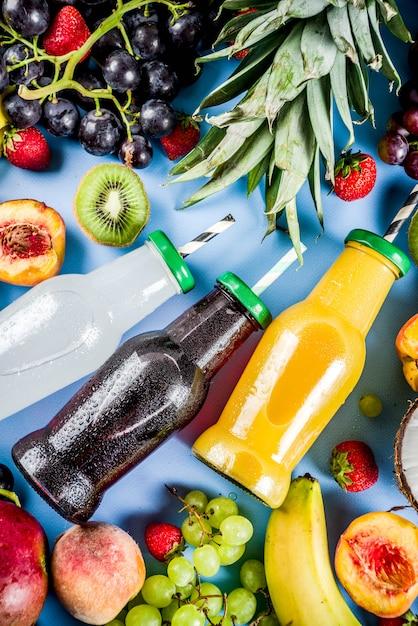 Verschiedene fruchtsäfte smoothies-konzeptsommer-vitamine nähren mit tropischen früchten und beeren auf einem hellen hintergrund Premium Fotos
