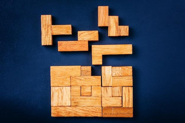 Verschiedene geometrische formenholzklötze ordnen in der festen figur auf einem dunklen hintergrund an. Premium Fotos