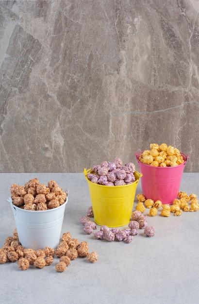 Verschiedene geschmacksrichtungen und farben von popcorn-bonbons, sortiert in bunten eimern auf marmor. Kostenlose Fotos
