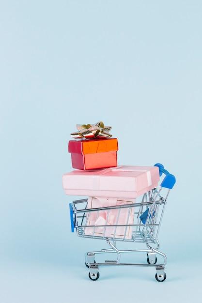 Verschiedene gestapelte pakete im einkaufswagen auf blauem hintergrund Kostenlose Fotos