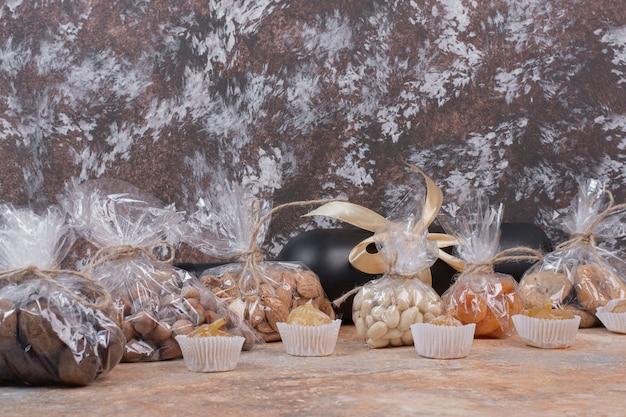 Verschiedene getrocknete früchte und nüsse in plastiktüte und flasche wein verpackt. Kostenlose Fotos
