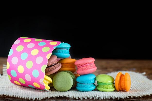 Verschiedene gewürzte macarons oder makrone in der papierschale auf dunklem hintergrund. Premium Fotos