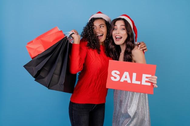 Verschiedene glückliche frauen mit bunten einkaufstaschen und rotem copyspace verkaufszeichen getrennt über blau Premium Fotos