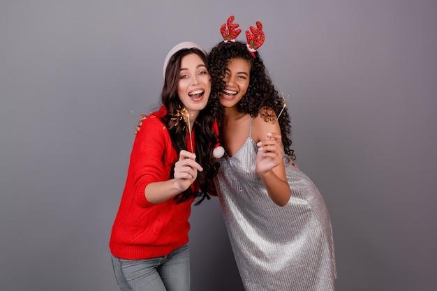 Verschiedene glückliche frauen mit den funkelnden wunderkerzen, die den weihnachtshut lokalisiert über grau tragen Premium Fotos