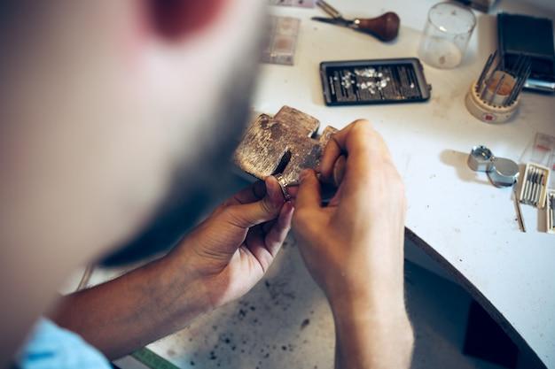 Verschiedene goldschmiedewerkzeuge am schmuckarbeitsplatz. juwelier bei der arbeit in schmuck. Kostenlose Fotos