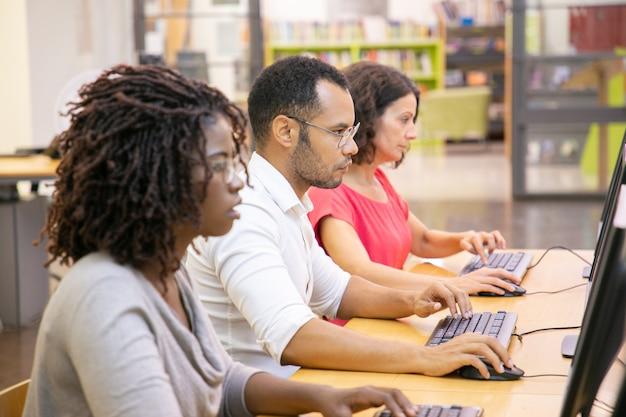 Verschiedene gruppe erwachsene studenten, die in der computerklasse arbeiten Kostenlose Fotos