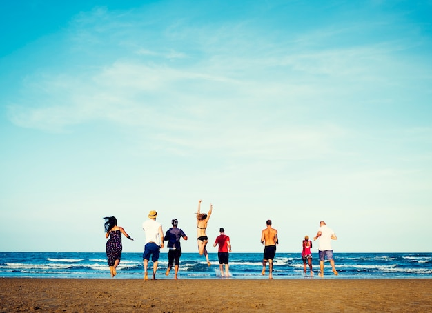 Verschiedene gruppe freunde, die zum strand laufen Kostenlose Fotos