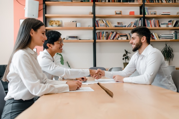 Verschiedene gruppe junge geschäftsleute, die hände auf einem abkommen im büro zusammenarbeiten und rütteln Premium Fotos