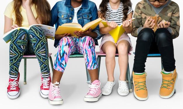 Verschiedene gruppe kinder, die in folge bücher sitzen sitzen Premium Fotos