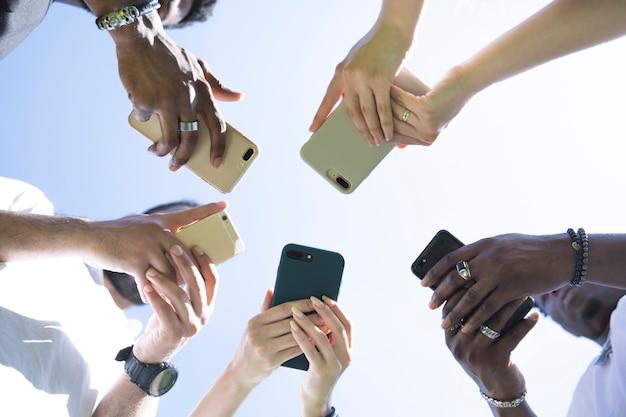 Verschiedene gruppe von freunden der ansicht von unten mit telefonen Kostenlose Fotos