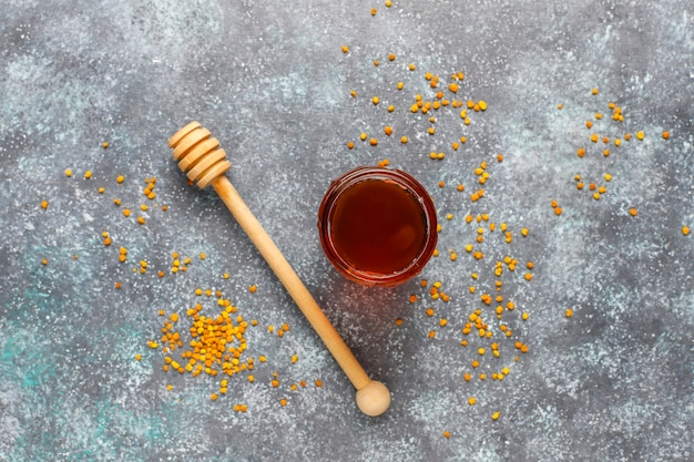 Verschiedene honigsorten in gläsern, waben und pollen. Kostenlose Fotos