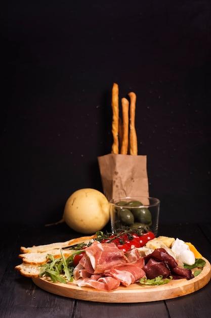 Verschiedene italienische vorspeisen: schinken, käse, grissini, oliven, obst Premium Fotos