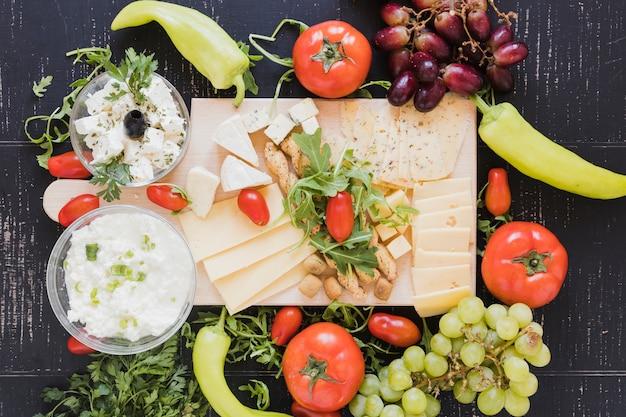 Verschiedene käsescheiben und -würfel mit trauben, tomaten; grüne chilis; rucola blätter und petersilie auf schwarzem hintergrund Kostenlose Fotos