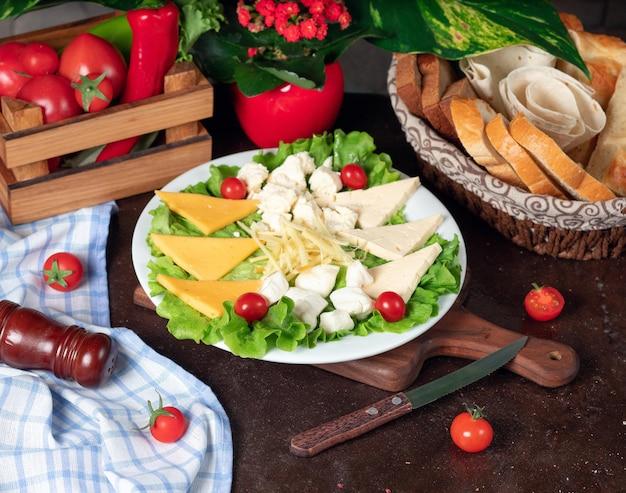 Verschiedene käsesorten befinden sich auf einem holzbrett und sind mit kirschtomaten, salat und frischem brot dekoriert. Kostenlose Fotos