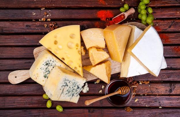 Verschiedene käsesorten mit honig, nüssen und gewürzen Premium Fotos