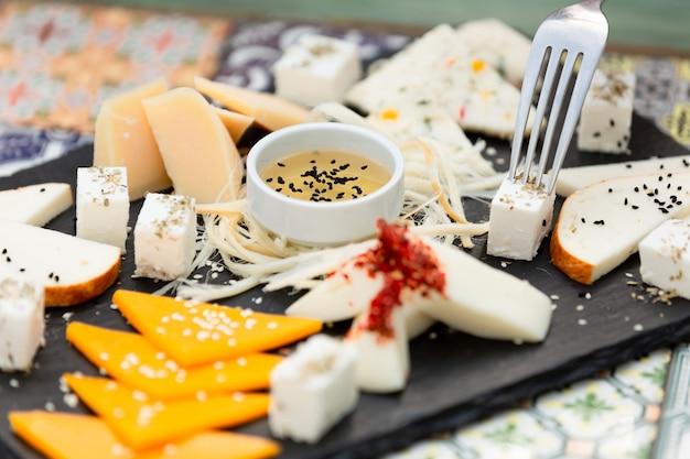 Verschiedene käsesorten mit honig schneiden Kostenlose Fotos
