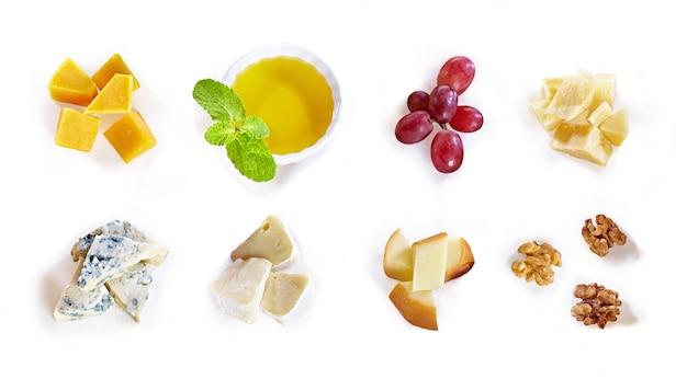 Verschiedene käsesorten mit honig, trauben, nüssen auf weißem hintergrund. draufsicht. blauschimmelkäse-, cheddar-, parmesan-, maasdam- und brie-käsescheiben Premium Fotos