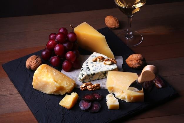 Verschiedene käsesorten, nüsse, trauben, geräuchertes fleisch und ein glas wein. Premium Fotos