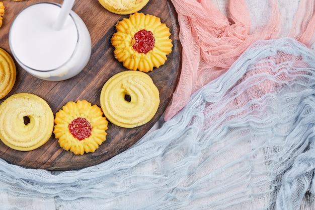 Verschiedene kekse und ein glas milch auf holzteller mit tischdecken. Kostenlose Fotos