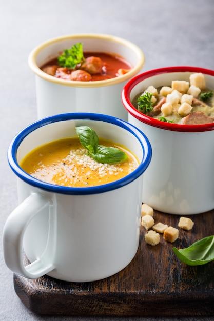 Verschiedene köstliche hausgemachte suppen in emaille-bechern mit zutaten. gesundes nahrungsmittelkonzept Premium Fotos