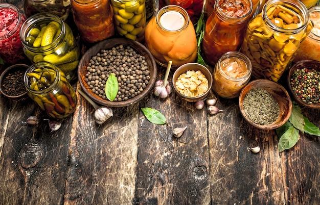 Verschiedene konservierte gemüse aus gemüse und pilzen in gläsern auf holztisch. Premium Fotos
