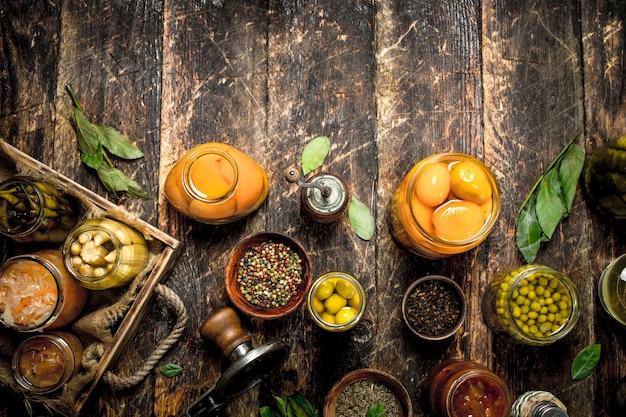 Verschiedene konservierte gemüse und pilze mit seemann und gewürzen auf holztisch. Premium Fotos