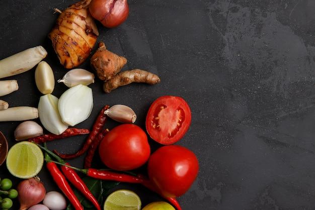 Verschiedene kräuter und zutaten zum kochen auf dunklem hintergrund. Premium Fotos