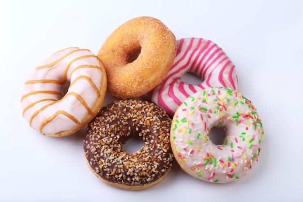 Verschiedene leckere hausgemachte donuts in der glasur, bunte streusel und nüsse. Premium Fotos