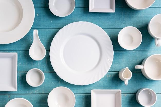 Verschiedene leere weiße platten und schüsseln auf hölzernem backgroun Premium Fotos