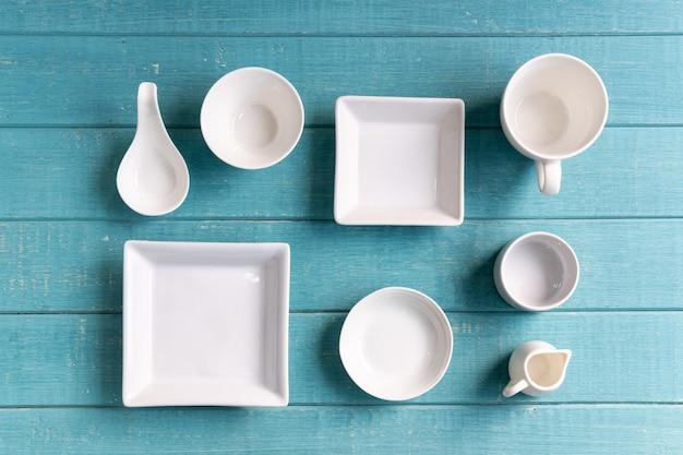 Verschiedene leere weiße platten und schüsseln auf hölzernem hintergrund, draufsicht Premium Fotos