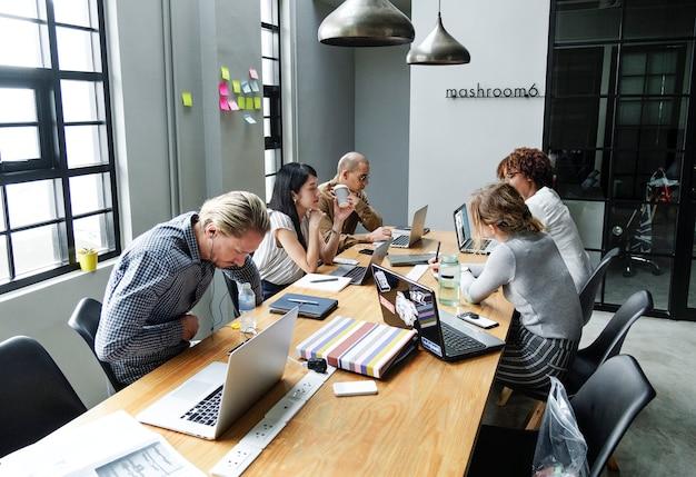 Verschiedene leute, die in einem büro arbeiten Kostenlose Fotos