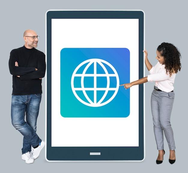 Verschiedene leute, die neben einer tablette mit www-ikone stehen Kostenlose Fotos