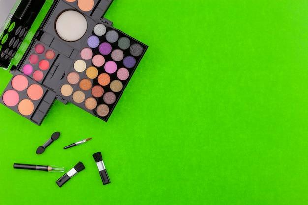 Verschiedene make-up pinsel, lidschatten und kosmetik auf bunten grünbuch hintergrund Premium Fotos