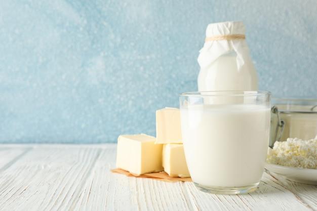 Verschiedene milchprodukte auf weißem holztisch gegen blauen raum, kopierraum Premium Fotos