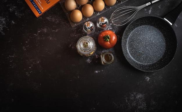 Verschiedene nahrungsmittelbestandteile auf einem dunklen hintergrund mit einem platz für text oder mitteilung Premium Fotos