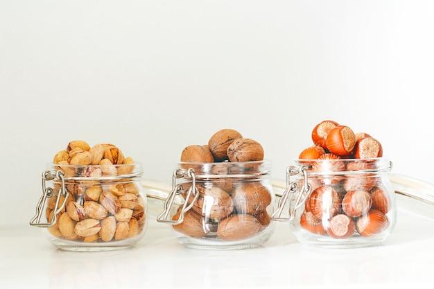 Verschiedene nüsse auswahl: haselnüsse, pistazien und pekannüsse im glas Kostenlose Fotos