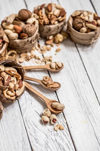 Verschiedene nüsse in platten und holzlöffel nahaufnahme auf weißem holzhintergrund, konzept der gesunden proteinkraft Kostenlose Fotos