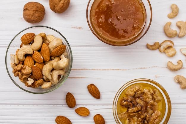 Verschiedene nüsse mit honig auf dem tisch Kostenlose Fotos