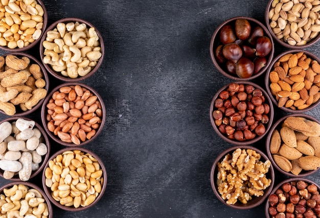 Verschiedene nüsse und getrocknete früchte in kleinen schalen mit pekannuss, pistazien, mandel und erdnuss flach legen Kostenlose Fotos