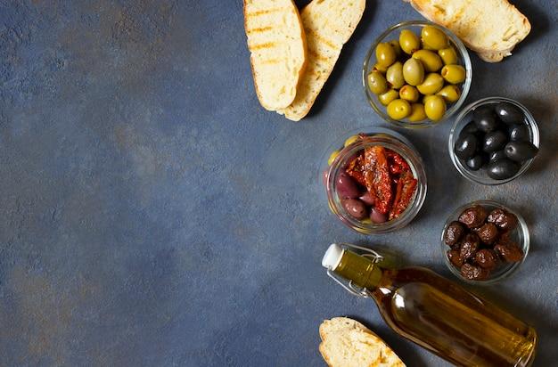 Verschiedene olivensorten, bruschetta, getrocknete tomaten und olivenöl. mediterrane snacks. ansicht von oben. dunkler hintergrund. Premium Fotos