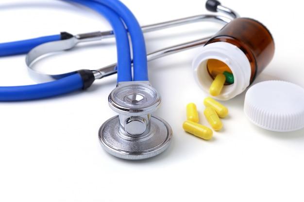Verschiedene pillen und ein stethoskop auf weißem hintergrund. Premium Fotos