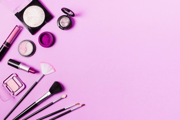 Verschiedene pinsel und kosmetika in lila tönung Premium Fotos
