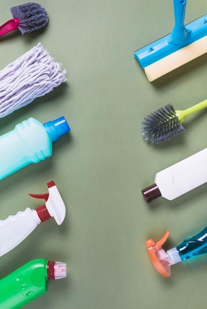 Verschiedene reinigungsausrüstungen vereinbarten in folge auf grünem hintergrund Kostenlose Fotos